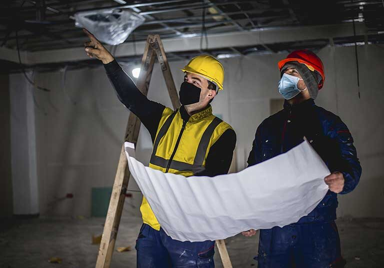 Two Construction Workers With Facemask Checking The Blueprints